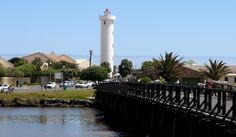 The wooden bridge leading to Woodbridge Island in Cape Town, with Milnerton Lighthouse in the background Beach Accommodation, Virgin Atlantic, Cape Town South Africa, Table Mountain, Most Beautiful Cities, Small Houses, Lighthouses, Homeland, Seattle Skyline