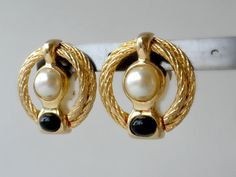 This is a large pair of 1980s round gold tone clip on earrings with faux pearl and black plastic accents.  Measure: 1.25 inches long x 1.25