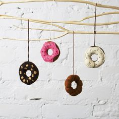 et of donut ornaments includes 1 pink iced with sprinkles, 1 chocolate with vanilla icing and sprinkles, 1 chocolate with nuts, and 1 cruller. Each of these ornaments have a string attached so they are ready for hanging. They are also available without the string attached. Listing is for a set of 4 donut ornaments.  Material: Made of eco felt which is made from 100% post consumer recycled plastic bottles and polyester fiberfill.