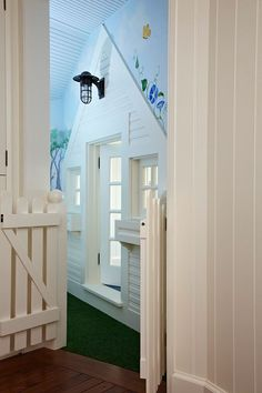 Utilize eaves in an attic to build a child's playroom, complete with door and windows, entry gate, and green carpet for grass