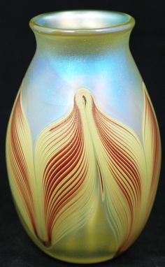 Josh Simpson iridescent art glass vase. Has red line design on yellow background. Signed and dated 1979  on the bottom. Measures 4 7/8 inches in height