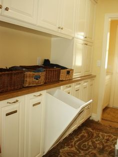 Laundry room with a row of individual pull-out hampers under the counter.  Perfect for sorting.  by Evans Woodworking Inc