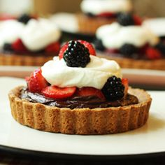 Chocolate Ganache Berry Tartelettes. Crisp tart shell filled with smooth ganache and topped with fresh summer berries and cream.