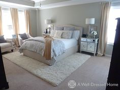 Soft neutrals, mirrored night stands, and rug.
