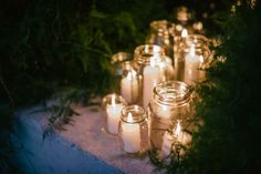 Masses of old jam jars filled with candles and surrounded by foliage. Ruby & Daniel / Wedding Style Inspiration / LANE