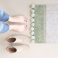 Greet house guests with a cheery pom pom doormat!