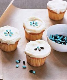 Arrange decorative candies or chocolate covered sunflower seeds in flowers atop a frosted cupcake.
