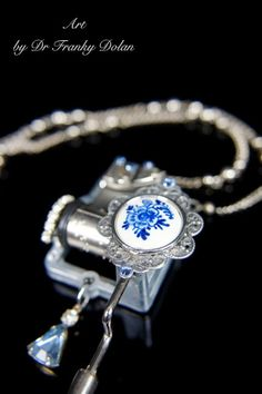"""An old hand-painted Delft porcelain relic is placed atop this music box movement. It is surrounded by a century-old watch piece, vintage rhinestone jewels, and perfect little kisses of Swarovski blue and clear crystals. The rare vintage chain has links of shiny metal pearls, 20"""" in length, that nicely hold up the 2"""" x 3"""" focal pendant piece. This not only sings, but it dances on your body as you grace about. - www.FaeFactory.com"""