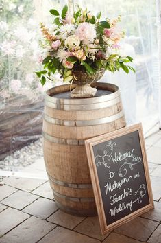 Wine barrel with floral arrangement & chalkboard