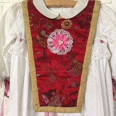 """En moderne dåpssmekke med kinesisk vri. Smekken """"frisker"""" opp en hvit dåpskjole sydd av bomull pyntet med engelsk blonde. Fra : staselig.no"""