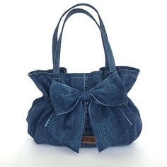 This gorgeous bow bag is one of my recycled bags collection. I made it from a blue jean pant. Ruffles close to the top make this handbag more eye catching. I made its big bow using the same fabric and attached it to the front side. I left some of edges unfinished. This handbag has a