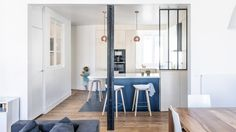 Anne‐Laure Dubois has renovated a family apartment in Paris, using dark blue tiles and poplar plywood to offset the existing wooden flooring