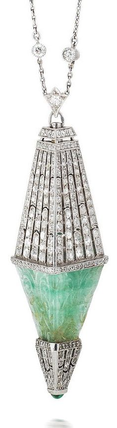An Art Deco emerald and diamond pendant necklace, circa 1920. Of hexahedral form, set with a carved emerald pyramid between a finely pierced surmount and terminal millegrain-set with old brilliant, single and rose-cut diamonds, with a triangular cabochon emerald finial, suspended from a fine trace-link chain with two old brilliant-cut diamond highlights, indistinct maker's mark, length of pendant 6.0cm. #ArtDeco #pendant