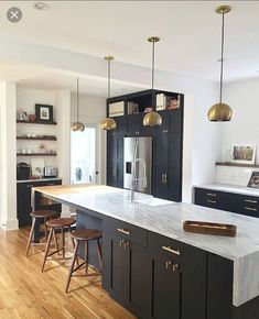 setup...kitchen wall > island. two parallel lines. marble waterfall. dark cabinets. light wood floor.