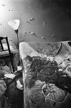 Photograph of the apartment of Fred Hampton, after the raid where he was killed by members of the Chicago Police Department. Photo shows large amount of blood on the bed that he was lying in when he was initially shot, and numerous bullet holes in the walls of the room.