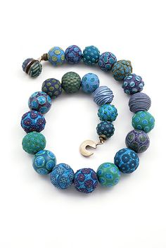 """""""Small Bead Necklace in Blues"""" created by #artists David Forlano & Steven Ford. A collection of ideas and techniques whereby the clay is applied, carved, sanded, polished, textured, and washed with oil paint in some cases."""