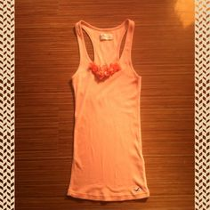 Peach Hollister Tank Top with Flower Ruffles This cute, peach, Hollister tank top is absolutely perfect for any season! It has a cute flowery detail at the neckline. It is a size small. It would be perfect to wear alone or to throw a cardigan over! Check it out! Hollister Tops Tank Tops