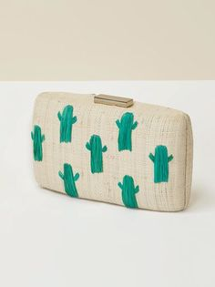 "Going on vacation? Take me with you. This is a straw clutch with hand embroidered cacti and a gold clasp. KAYU bags are carefully handcrafted by women in the Philippines, Indonesia and Malaysia, preserving their indigenous crafts as well as providing them with a living wage.   Measurements: Width: 8"" Height: 4.5"" Depth: 2"""