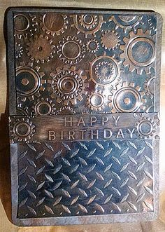 "My son loves the texture of this card - says it's so ""lifelike"" he expected it to feel like metal. Embossing Folders: Darice - Steampunk Cogs Background Darice - Diamond Plate Darice - Happy Birthday Cardstock Grey Hammered Card - PayPer Box Silver Mirror Foil Card (sanded down)- Home Bargains Ink: Tsukineko Brilliance 3 Colour Ink Pad, Tiramisu I used black over brown for a rusted appearance."