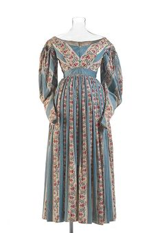 A full-length dress made from opaque, lightweight fine cotton printed with blue stripes and a geometric floral design. The dress has a tight fitting slightly high waisted bodice, voluminous sleeves, and a long gathered skirt. 1800s Fashion, 19th Century Fashion, Victorian Fashion, Vintage Fashion, Antique Clothing, Historical Clothing, Historical Dress, Vintage Outfits, Vintage Dresses
