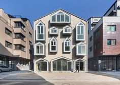 Mixed-use building in South Korea featuring a facade of house-shaped windows.