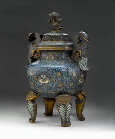 Large and very rare Imperial Chinese cloisonné and gilt bronze censer, Qing dynasty, 17th / 18th century. The censer's body of rounded square form and raised on four leaf-form legs issuing from intricately-cast gilt bronze lingzhi heads; the large handles of S-form: capped with cloisonné lingzhi heads and terminating in leaf-like mounts; the vented cover with elaborate gilt bronze grate and surmounted by unique gilt bronze natural lingzhi-form finial. #FreemansAuction