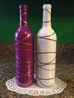 Spray paint wine bottles brown or mirror finish. Maybe twit 2 rubber bands together, then place on the wine bottles. Spray paint purple or green on top. Hoping for a grape vine look.