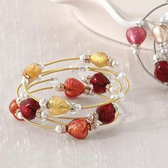 murano hear bracelet. Made in Murano, Italy, world-renowned for its glass-blowing artisans, this trio of spring-wire bangles features hand-made glass hearts with silver- and gold-leaf-finished interiors. Exclusively from RedEnvelope.