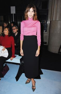 Alexa Chung in a pink turtleneck tucked into a long black skirt with python print cut-out slingback heels at London Fashion Week