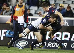 Jason Woodward of the Rebels is tackled by Clyde Rathbone of the Brumbies during the round 17 Super Rugby match between the Brumbies and the Rebels at Canberra Stadium on June 7, 2013 in Canberra, Australia.