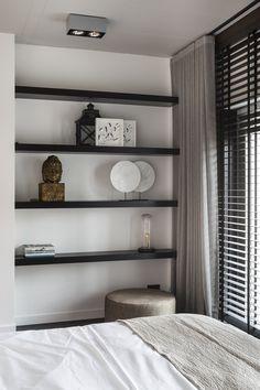 """Stijlvolle slaapkamer met houten jaloezieën van Zonnelux, gecombineerd met gordijnen. De donkere schappen steken mooi af tegen de witte muur. Foto: Denise Keus – """"Stijlvol Wonen"""" - © Sanoma Regional Belgium N.V."""