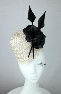 Champagne lacquered straw braid fascinator with black flower and arrowhead feather detail.