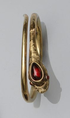 A Victorian serpent bangle  The sprung hinged bangle modelled as a coiled serpent, the scroll engraved head set with a pear-shaped cabochon garnet, with matching garnet eyes, inner diameter 5.2cm.