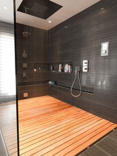 Banheiro com Box amplo com parede preta e piso em madeira
