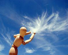 muñeco de madera jugando con las nues