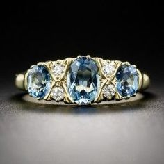 Designed and rendered in the classic Victorian style, but utilizing unconventional centerstones, in this case three lucent, deep pastel blue aquamarines, this extra lovely and eminently wearable jewel was crafted in Great Britain in rich 18K yellow gold and is currently ring size 7 1/4 +.