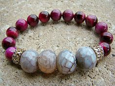 Amber brown crackle agate rondelle gemstones are surrounded by fuschia tigers eye gemstones and high quality textured European gold beads. MEMBER - BeJeweledByCandi