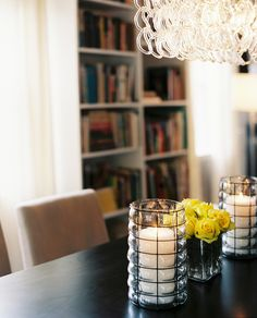 Details Contemporary Photo - Contemporary hurricane lanterns and a vase of yellow roses atop a dining table