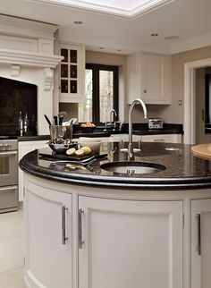 Audley kitchen with large circular white painted island with black granite top