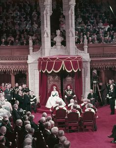 Queen Elizabeth II and Prince Phillip sit on thrones before a full Parliament.jpg