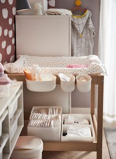 IKEA SNIGLAR baby changing table made of birch with attached ÖNSKLIG white plastic storage baskets holding diapers and baby changing supplies. A nursery with plenty of storage for our special ones Stitch nc_munich Kids room IKEA SNIGLAR baby changi