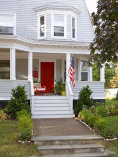 Use your front door to make a statement. Here, a bright red-painted door adds warmth to this home's soft gray facade.