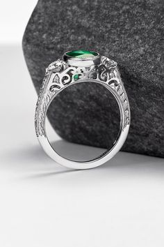 Create an engagement ring as unique as your love story! Get inspired by this vintage take on the classic trilogy - a ring by Taylor & Hart. Set in platinum, an oval emerald is paired with two round brilliant diamonds accented with lacy filigree. Hand engraving and milgrain delicately finish this vintage style.
