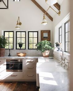 Love the black windows, beams and off white kitchen.