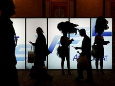People walk by showgirls at the entrance of the Global Gaming Expo in Las Vegas.