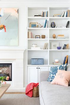 Beautiful living room features a white limestone fireplace tucked under a pink, orange and blue abstract art piece placed next to built in shelves lined with tchotchkes as well as cabinets adorned with bronze knobs. Fireplace Bookcase, Fireplace Built Ins, Home Fireplace, Limestone Fireplace, Fireplaces, Diy Living Room Decor, Living Room Designs, Living Room Inspiration, Home Decor Inspiration