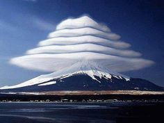 Mount Fuji Lenticular Clouds    Such extraordinary cloud formations are the result of high velocity or jet stream winds being forced over a barrier or mountain. The resultant laminar flow causes the air to move in wave-like layers. Waves develop above the mountain and on the leeward side. If the air contains sufficient moisture, characteristic standing-wave lenticular clouds will form.