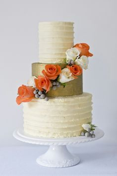 Buttercream wedding cake with gold lustre tier and fresh flowers