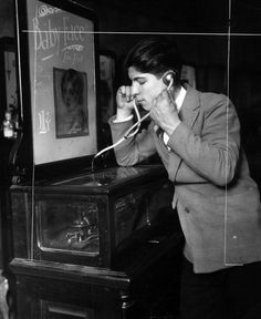 "Around the 1920s, phonographs became more public than just personal home devices. Here, a customer at Loewy's 1 cent arcade (14th street, New York) drops a cent in the slot to listen to a phonograph record. Not only did this increase the popularity of the phonograph, it also increased the size of the industry. In addition, what the man is using to listen to the record is a pair of small phonograph horns. These were then named ""ear-trumpets"" which set the model for modern headphones."