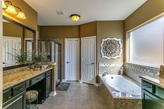 Luxurious Master Bath with gleaming Granite countertops, SEPERATE sinks- hers with her very own dressing area and decorative framed mirrors.